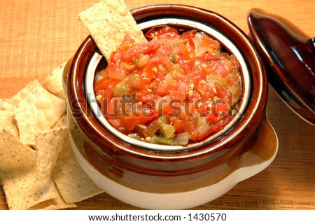 Salsa bowl with corn chips on a rustic table - stock photo