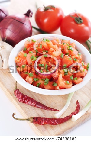 Salsa in a bowl on a wooden board and the ingredients: tomatoes, onions, garlic, chili pepper