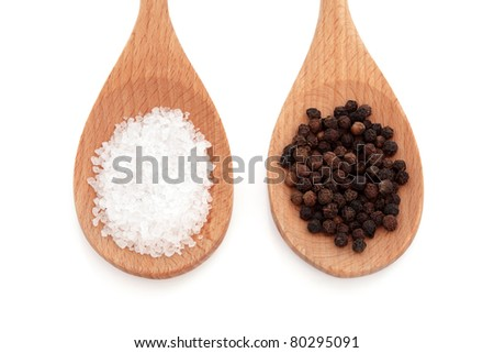 Salt and pepper in wooden spoons isolated over white background.