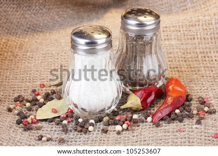 Salt and pepper mills and spices on burlap background