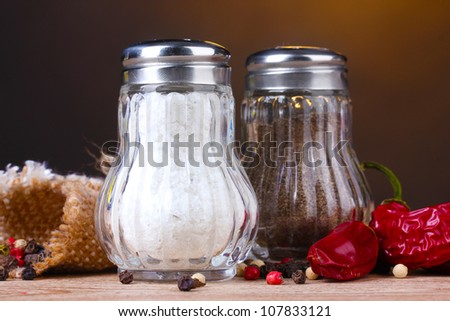 Salt and pepper mills and spices on wooden table on brown background