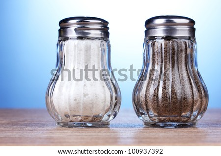 Salt and pepper mills on wooden table on blue background