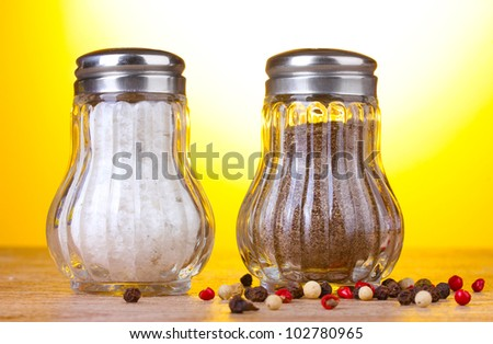 Salt and pepper mills on wooden table on yellow background
