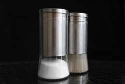 Salt and pepper shaker on black background