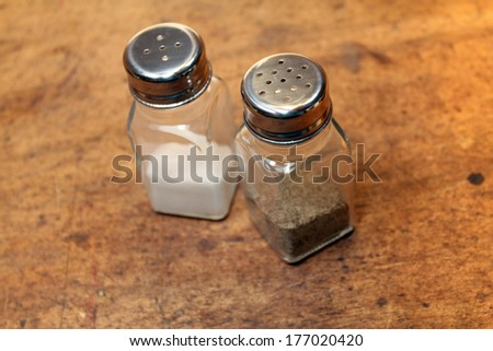 salt and pepper shakers over old wood background