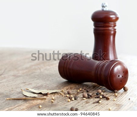 Salt and pepper shakers. Scattered around the spices on a wooden table.