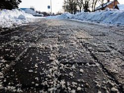 Salt grains on icy sidewalk surface in the winter. Applying salt to keep roads clear and people safe in winter weather from ice or snow, closeup view.