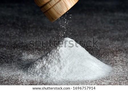 Salt grinder and pile of salt. Salt falls from the grinder on a table full of salt. Detail on grinder and white saltpyramid.