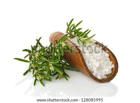 Salt in a wooden scoop and rosemary on a white background