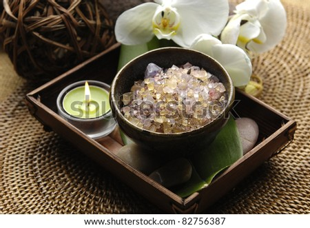 salt in bowl and candle in basket and orchid with on burlap mat