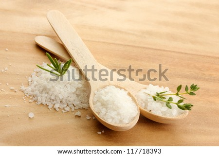 salt in spoons with fresh  rosemary and thyme on wooden background