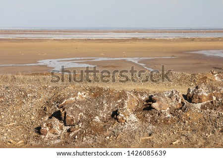 Salt lake shore landscape. clear weather. nature reserve. combination of blue and beige. brownish land, dry land. earth. water in distance. color layers #1426085639