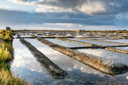 Salt marshes on the island of Noirmoutier in France.The sun rises on ponds, basins and salt piles