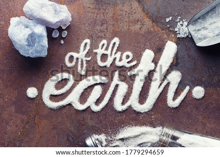 Salt of the Earth - 'of the earth' in calligraphy written in salt on a rusty metal background. With salt crystals, old style salt shaker and measuring spoon around the edges of the image