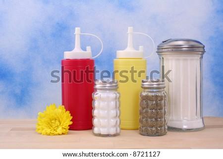 Salt, Pepper, Sugar and Mustard on Blue Textured Background