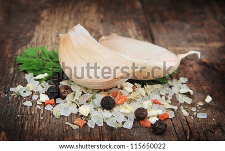 Salt pile and pepper and garlic on wooden texture