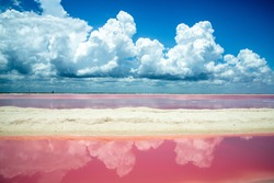 Salt pink lagoon against the blue sky with clouds reflecting in the water. Las Coloradas, Yucatan, Mexico