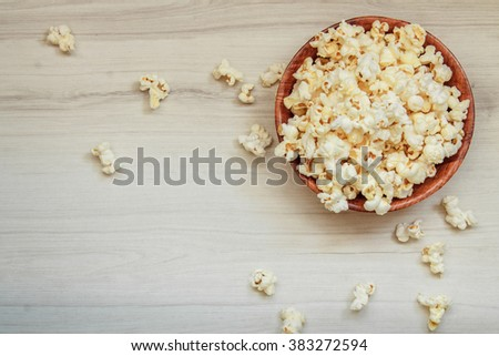 Salt popcorn on the wooden table. Popcorn in a wooden bowl. Watching a movie with popcorn. Copy space. Pop corn. Top view. Flat lay.
