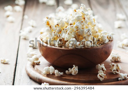 Salt popcorn on the wooden table, selective focus