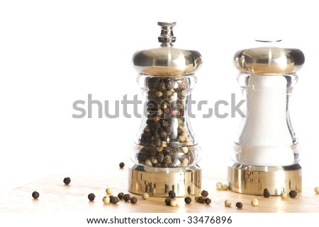 salt shaker and pepper mill on wood cutting board