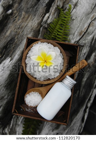 salt with frangipani in bowl spoon with bamboo grove with massage oil on driftwood