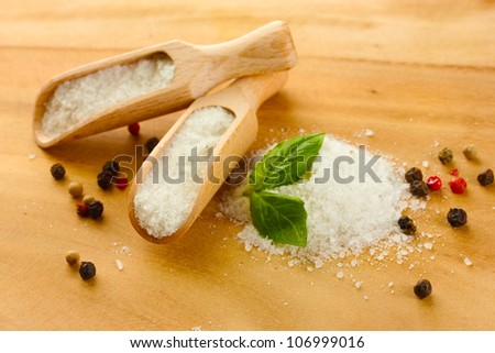 salt with fresh basil and and pepper on wooden table