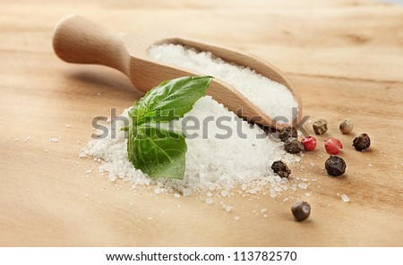 salt with fresh basil, garlic and pepper on wooden table