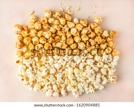 Salted and caramelized popcorn varieties on pastel colored background, top view, horizontal orientation