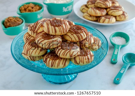 Salted caramel thumbprint cookies drizzled with chocolate sitting on decorative blue glass pasty stand and additional cookies on white plate surrounded by ingredients in blue and white measuring cups