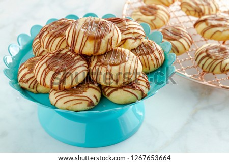 Salted caramel thumbprint cookies drizzled with milk chocolate sitting on bright blue pastry and copper cooling rack in background