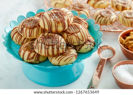 Salted caramel thumbprint cookies drizzled with milk chocolate sitting on bright blue pastry stand surrounded with ingredients