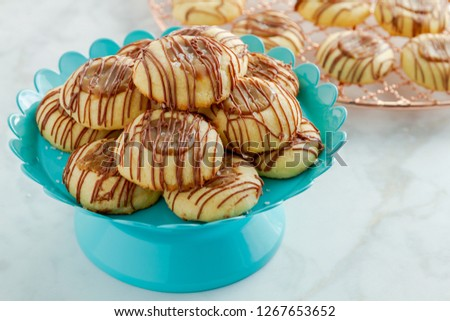 Salted caramel thumbprint cookies drizzled with milk chocolate sitting on bright blue pastry stand