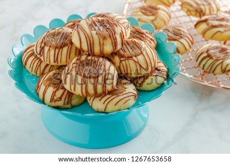 Salted caramel thumbprint cookies drizzled with milk chocolate sitting on bright blue pastry stand and copper cooling rack
