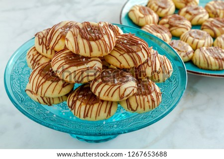 Salted caramel thumbprint cookies drizzled with milk chocolate sitting on decorative blue glass pasty stand and additional cookies on blue plate in background
