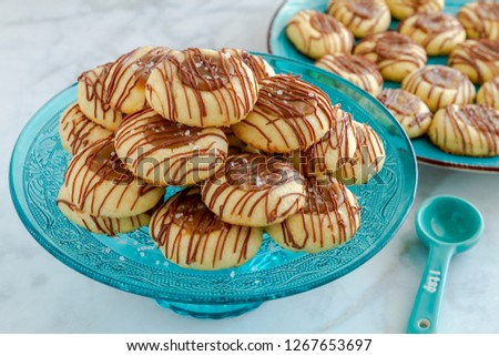 Salted caramel thumbprint cookies drizzled with milk chocolate sitting on decorative blue glass pasty stand and additional cookies on blue plate in background with blue measuring spoon on side