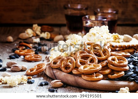Salted straws in the shape of pretzels, popcorn and other salty snacks, junk food, snacks, for beer or cola, old wooden background, selective focus