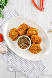 Saltfish Fitters served with sauce, styled shoot.