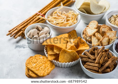 Salty beer snacks in whit bowls #687989542