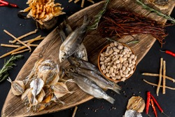 Salty dried fish roach and yellow stripe scad fish with dried fish sticks and pistachios on wooden board on black table background. Top view.
