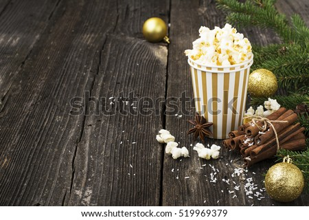 Salty fresh crusty homemade popcorn in silver paper cup in the fashion light background of white brick wall in a New Year\'s interior with silver Christmas balls. selective focus