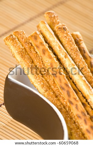 Salty sesame sticks in dish and on table cover.