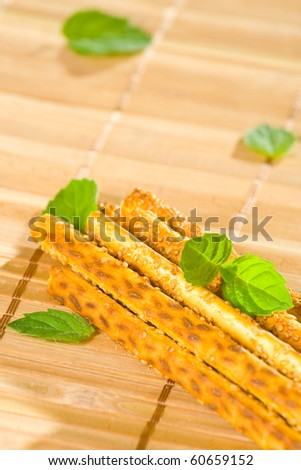Salty sesame sticks on table cover with mint leaves.