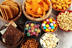 Salty snacks. Pretzels, chips, crackers in wooden bowls. Unhealthy products. food bad for figure, skin, heart and teeth. Assortment of fast carbohydrates food.
