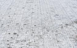 Salty surface, salt on paving slabs outdoors. White salt stains on pedestrian paving slabs. Rock salt (sodium chloride) used on paving slabs and asphalt roads for deicing. Salt is de-icing agent