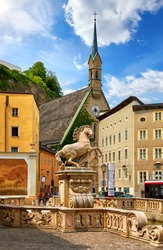 Salzburg, Austria. Horse Pond statue fountain monument at Herbert von Karajan Square, Statue of horse, tower of chapel in sanctuary among old austrian buildings. Sunny summer day. Blue sky.
