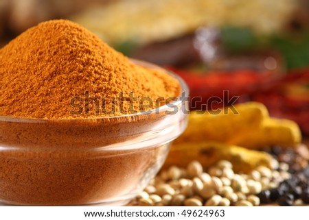 Sambar curry powder in a glass bowl along with all spice ingredients