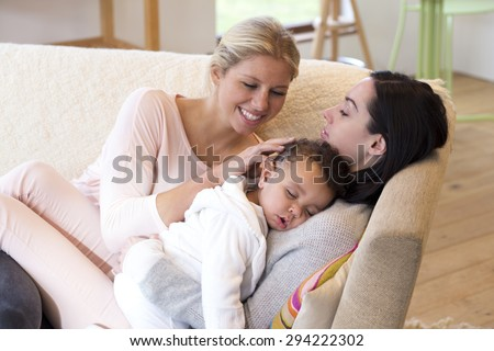 Same sex female couple lying down with their baby son #294222302