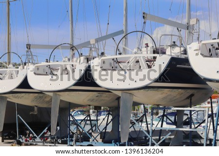 Same yachts stand in a row on the dry parking in the marina on a sunny summer day. Device sailing vessel below the waterline. Stern sports boat. Mediterranean city. Preparing for the sailing charter #1396136204