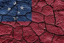 Samoa flag on a mud texture of dry crack on the ground