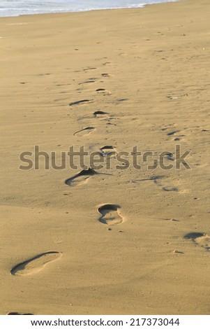 Sampieri, IT, February 2, 2013: walking on a Sicilian beach. Footprints on the beach